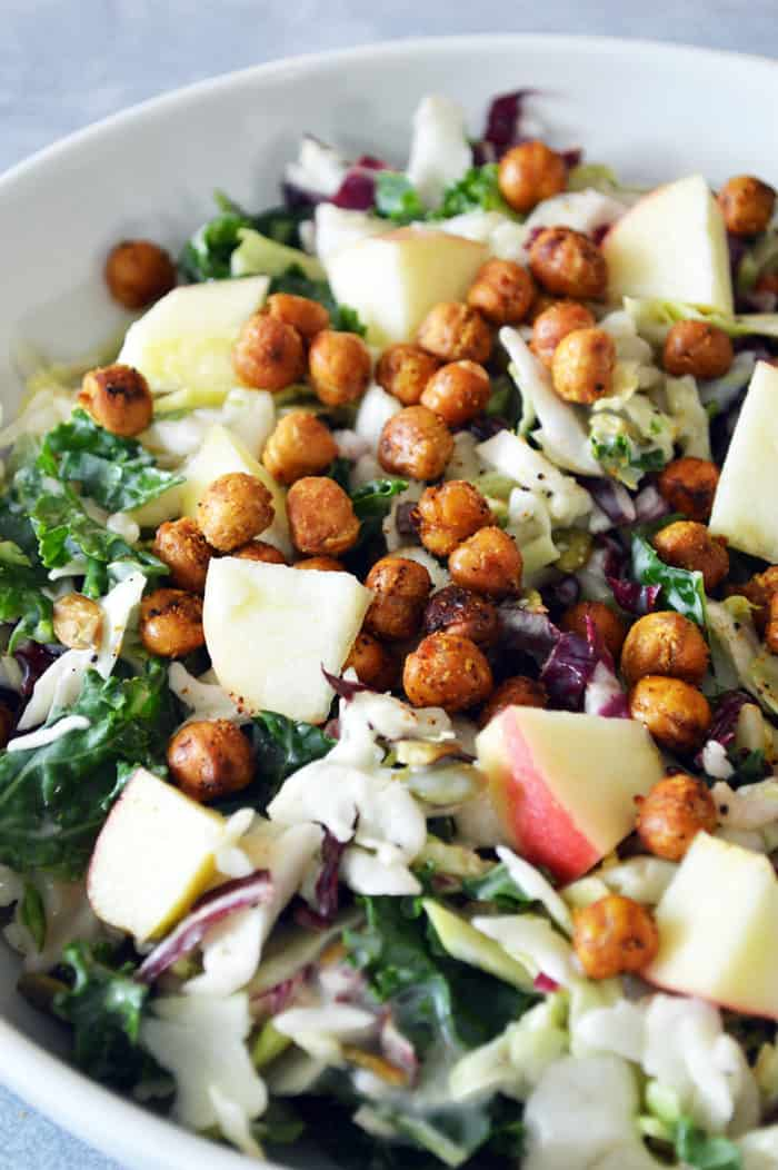 Close up of bowl of salad topped with roasted chickpeas and apples
