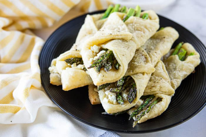 Asparagus puff pastry bundles on dark plate