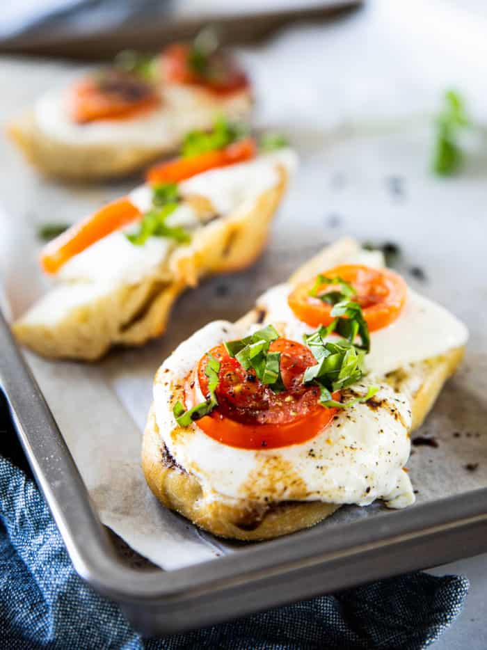 Close up of french bread pizzas topped with mozzarella, tomatoes and basil on baking sheet