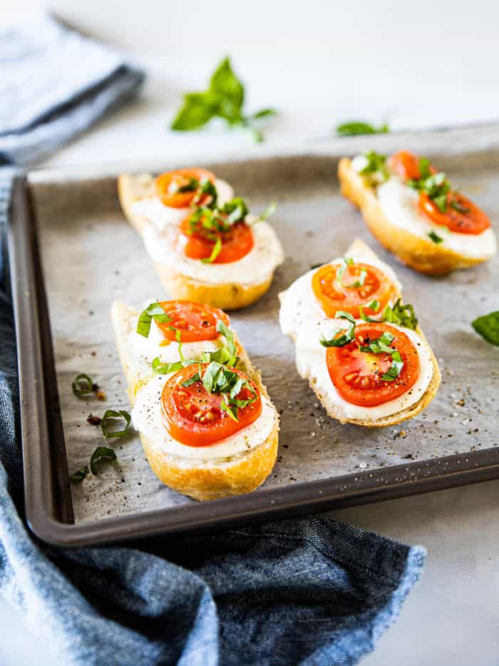 French bread pizzas topped with mozzarella, tomatoes and basil on baking sheet