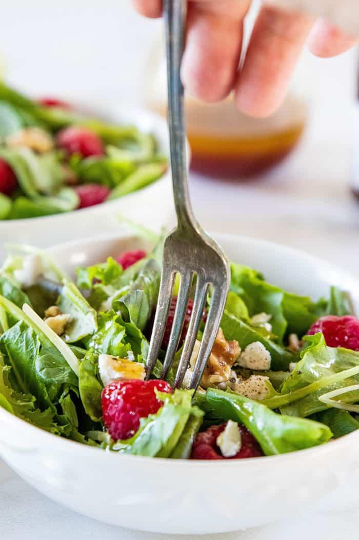 Fork digging into salad