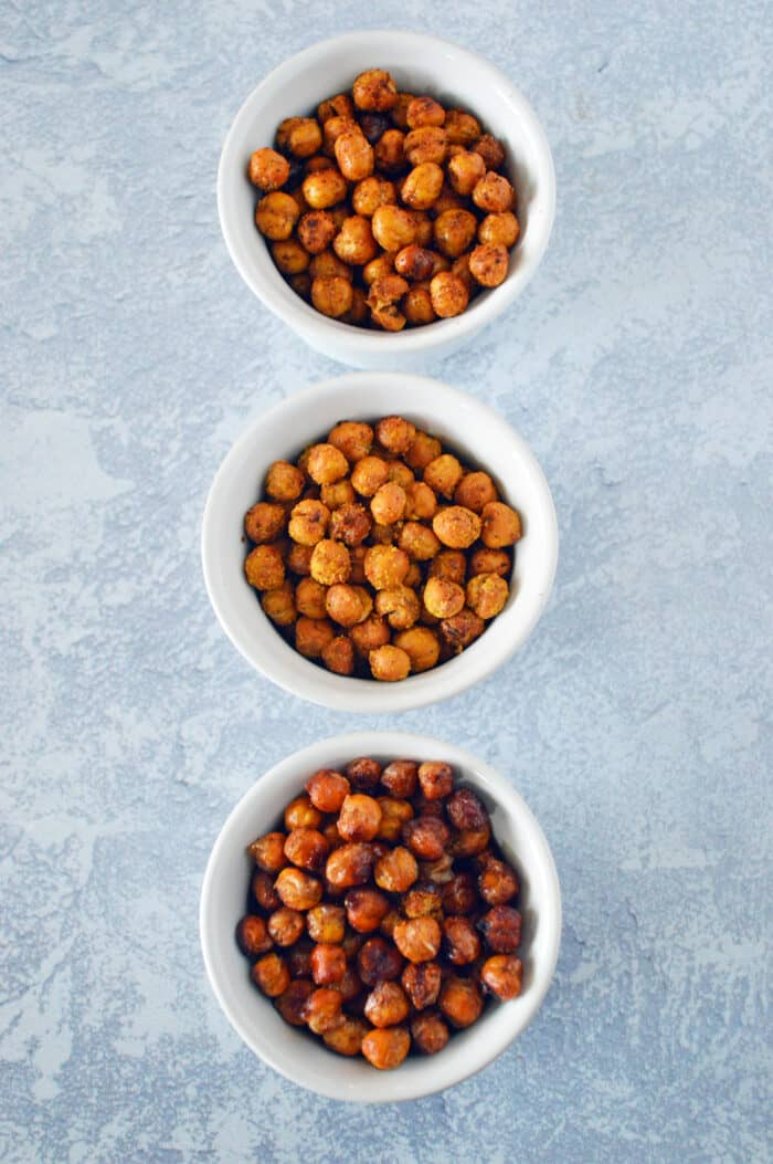 3 bowls of roasted chickpeas on marble counter