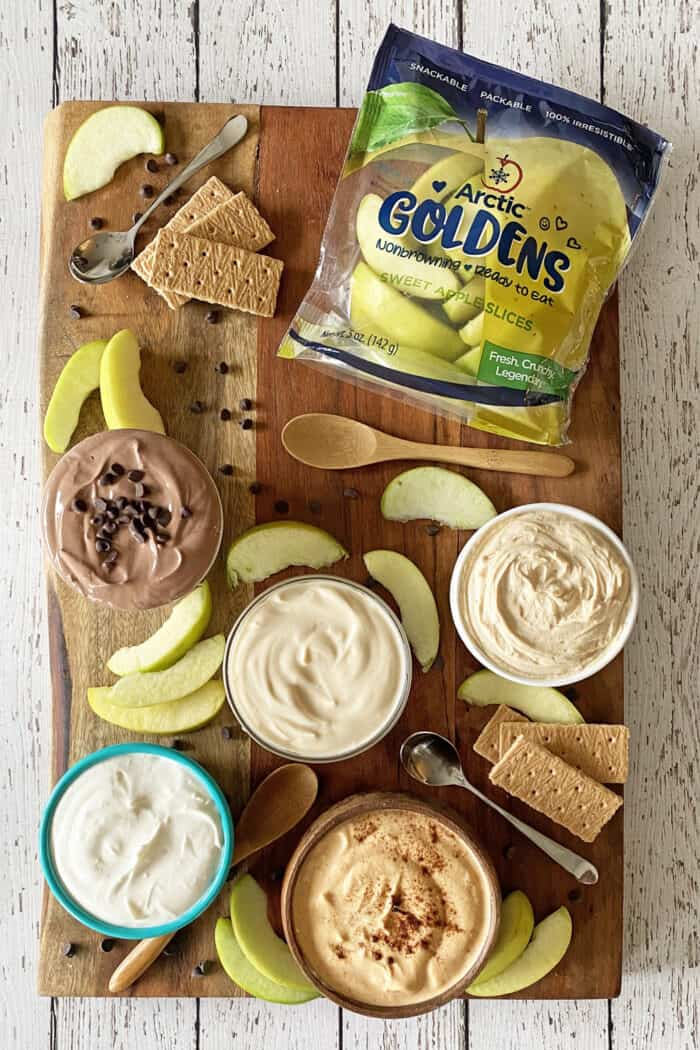 Snack board with bowls of yogurt dip, sliced apples, graham crackers and bag of sliced apples.