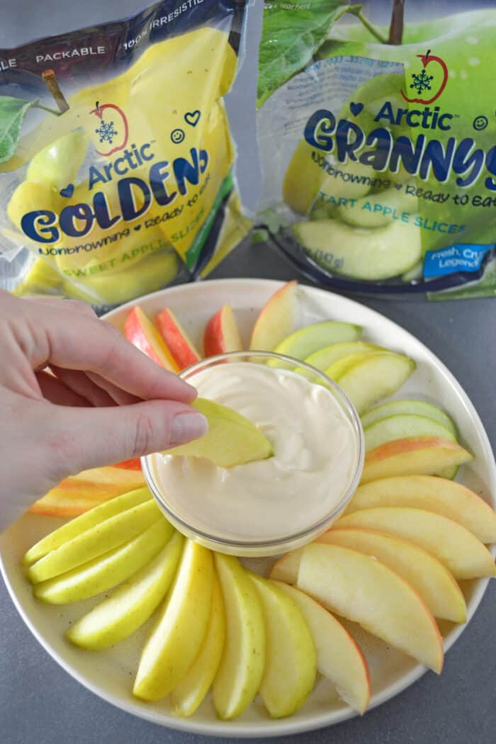 Hand dipping sliced apple into a bowl of caramel yogurt fruit dip with plated with sliced apples. Bags of sliced apples in background.
