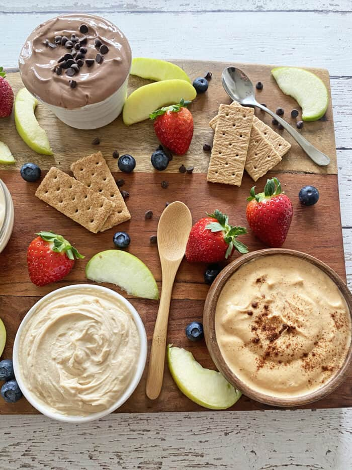 Close up of snack board with fruit dips in bowls, sliced apples, strawberries, blueberries and graham crackers.
