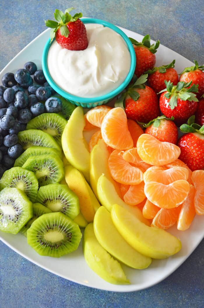 Bowl of cream cheese fruit dip plated with a rainbow of fruit, including blueberries, kiwi, apples, mandarins and strawberries.
