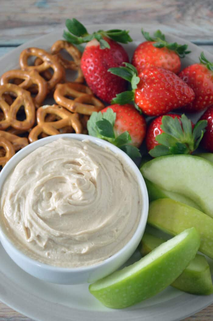 Bowl of peanut butter yogurt dip plated with sliced apples, strawberries and pretzels.