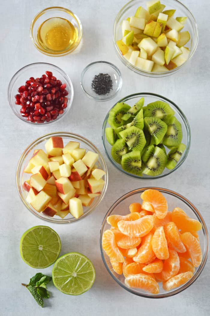 Ingredients for fruit salad laid out in individual glass bowls