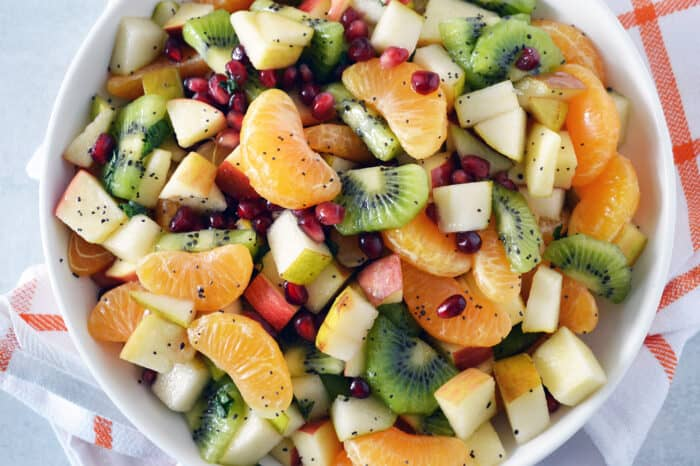 Fruit salad of mandarins, kiwi, apples, pears and pomegranate arils in white bowl with orange striped towel underneath