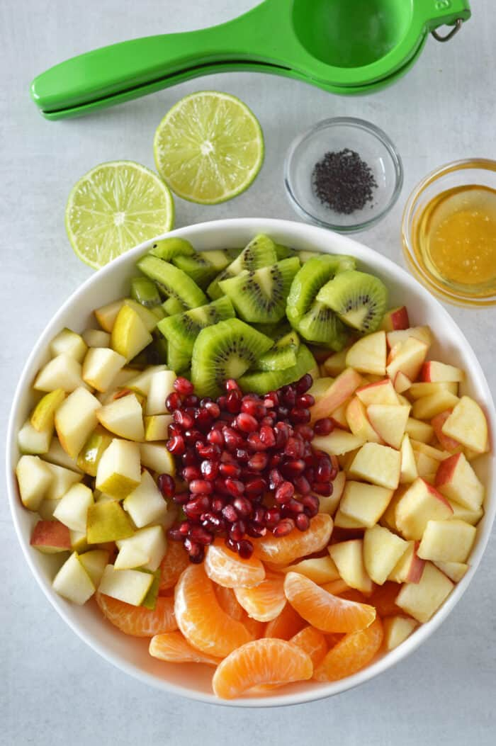 Kiwi, apples, mandarins, pears and pomegranate arils in white bowl with lime, poppy seeds and honey in background