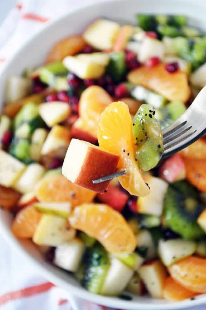 Close up of apple, mandarin and kiwi on fork. Bowl of fruit salad blurred in the background