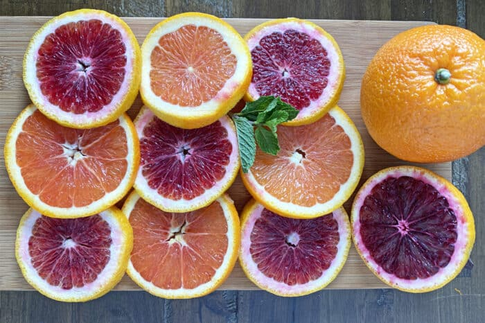 Slices of blood oranges and cara cara oranges on cutting board.