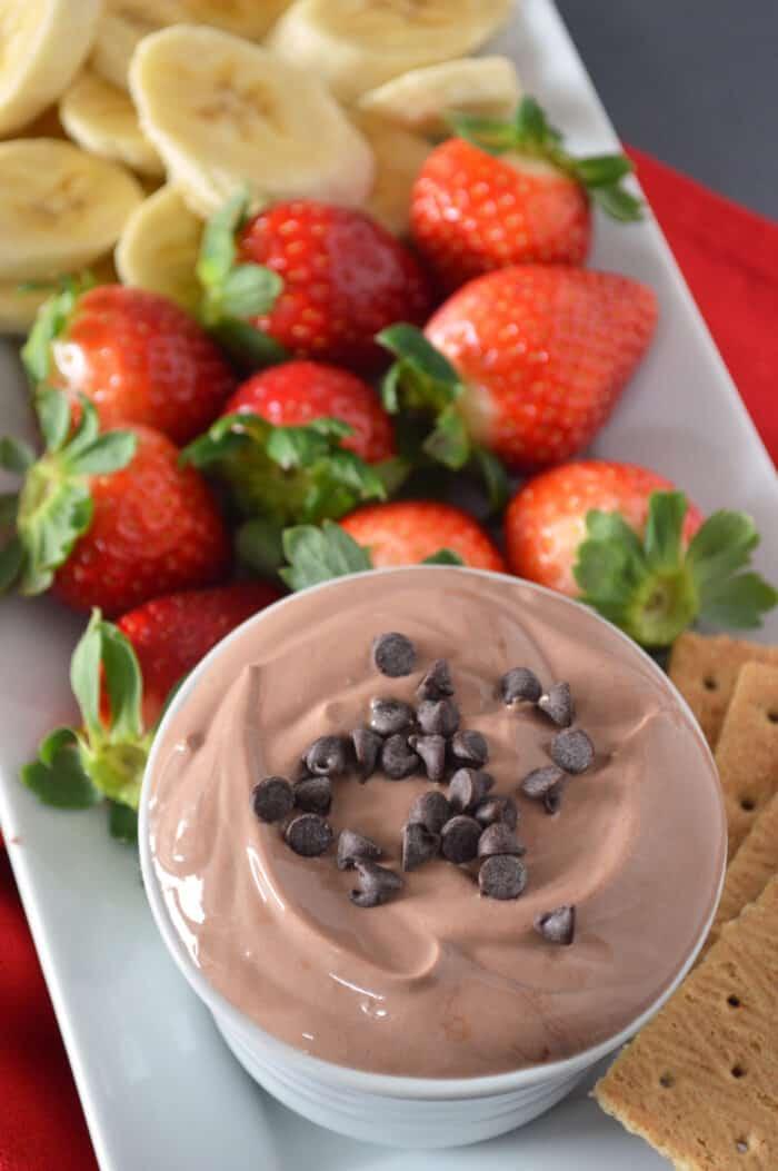 Bowl of chocolate yogurt dip plated with fruit.