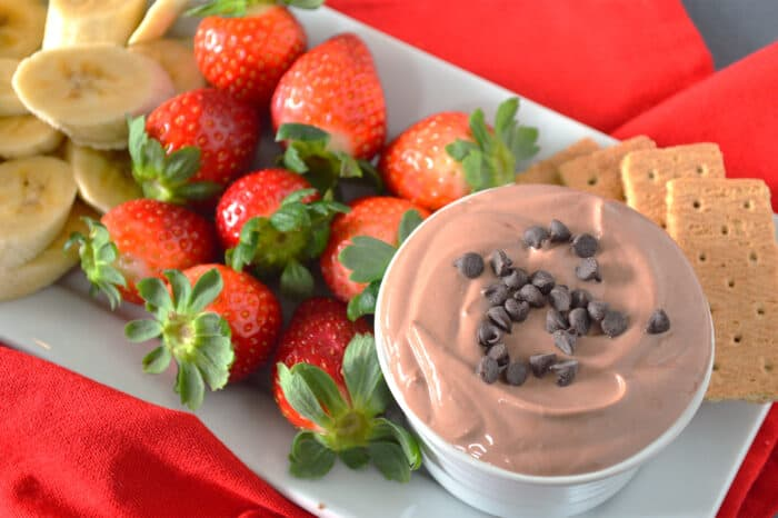 Bowl of chocolate yogurt dip topped with mini chocolate chips plated with graham crackers, strawberries and banana slices.