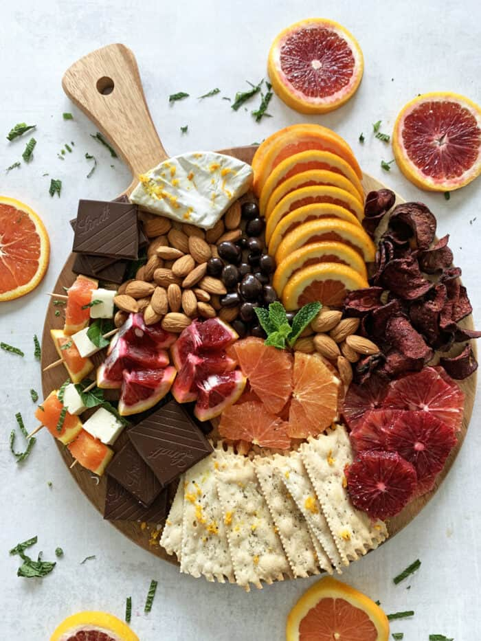 Grazing board with fresh citrus, chocolate, cheese, crackers, almonds, beet chips and more.