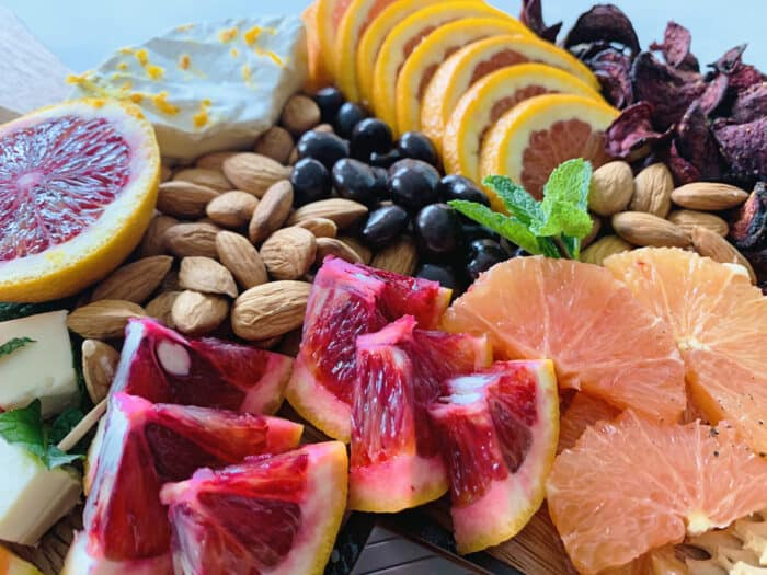 Close up of grazing board focusing on slices of blood oranges and cara cara oranges with almond and chocolate in the background.