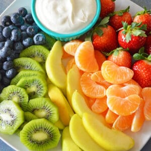 Cream cheese fruit dip in bowl plated with blueberries, kiwi, yellow apples, mandarins and strawberries.