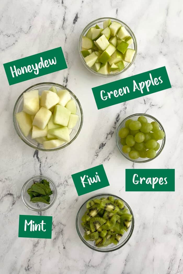 Green fruit salad ingredients in glass bowls.