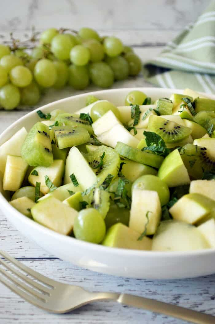 Close up of green fruit salad in white bowl. Fork placed in front of bowl and a bunch of green grapes in the background.