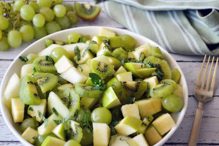 Close up of green fruit salad in white bowl.