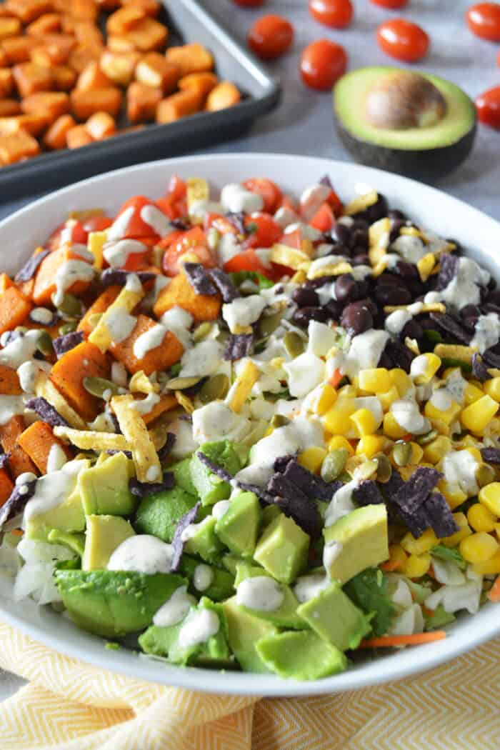 Sweet potato taco bowls plated in white bowl with sheet pan of roasted sweet potatoes and an avocado in background.