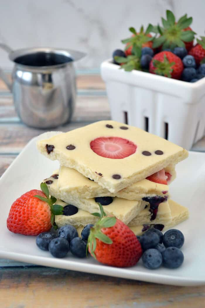 Stacked sheet pan pancakes on plate with fresh fruit.