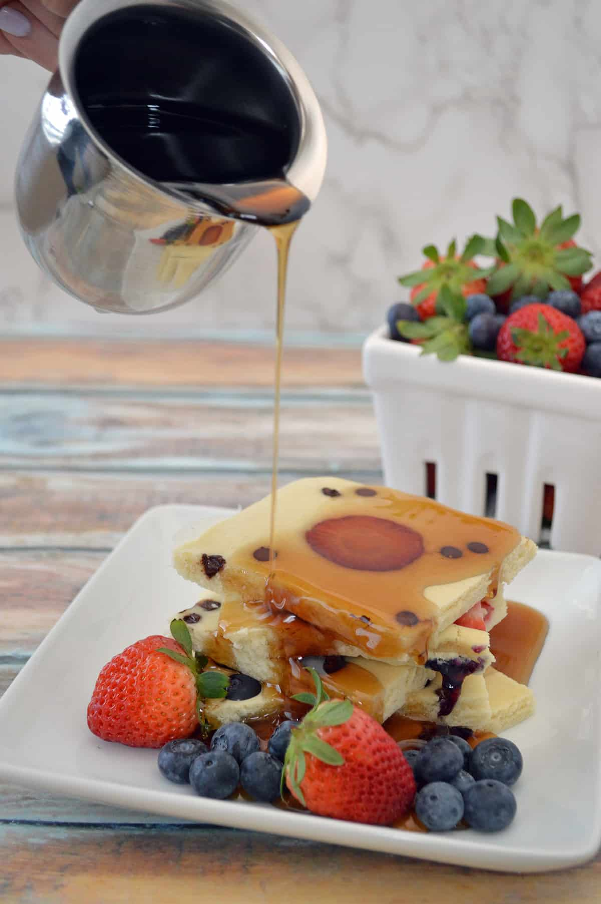 Syrup being poured on top of stack of sheet pan pancakes.