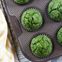 Overhead of green spinach muffins in muffins tin with yellow striped napkin.
