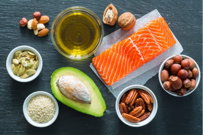Salmon, avocado, olive oil, nuts and other healthy fats on dark background.