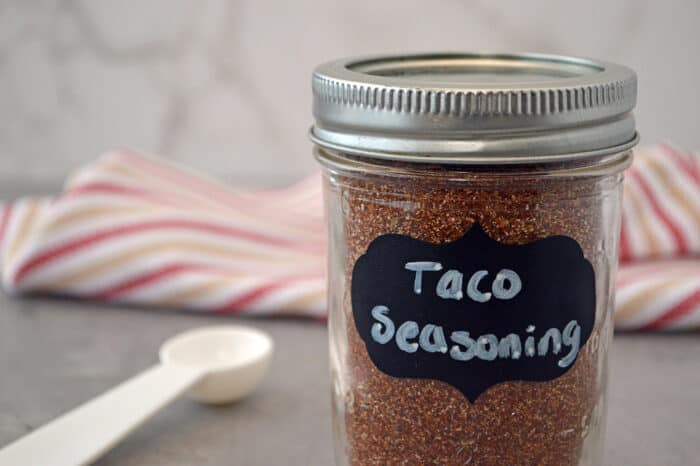 Mason jar of taco seasoning with measuring spoon.
