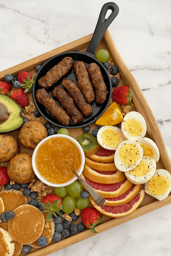 Close up of breakfast grazing board focusing on sausage links, hard-boiled eggs and fruit.