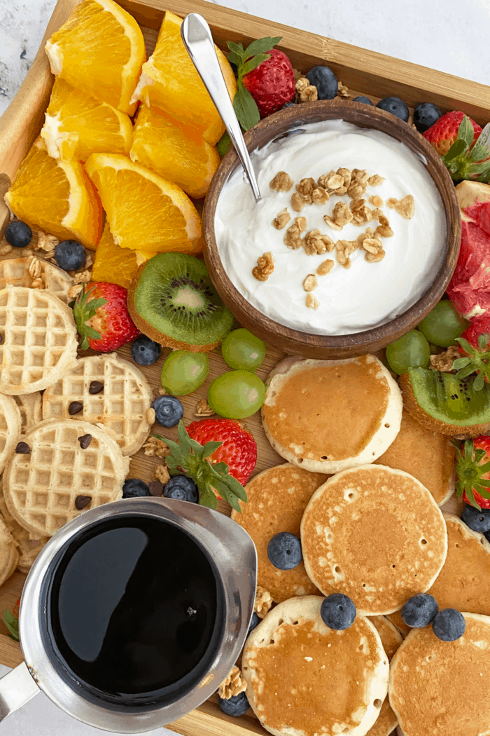 Close up of breakfast grazing board focusing on min pancakes and waffles with syrup.