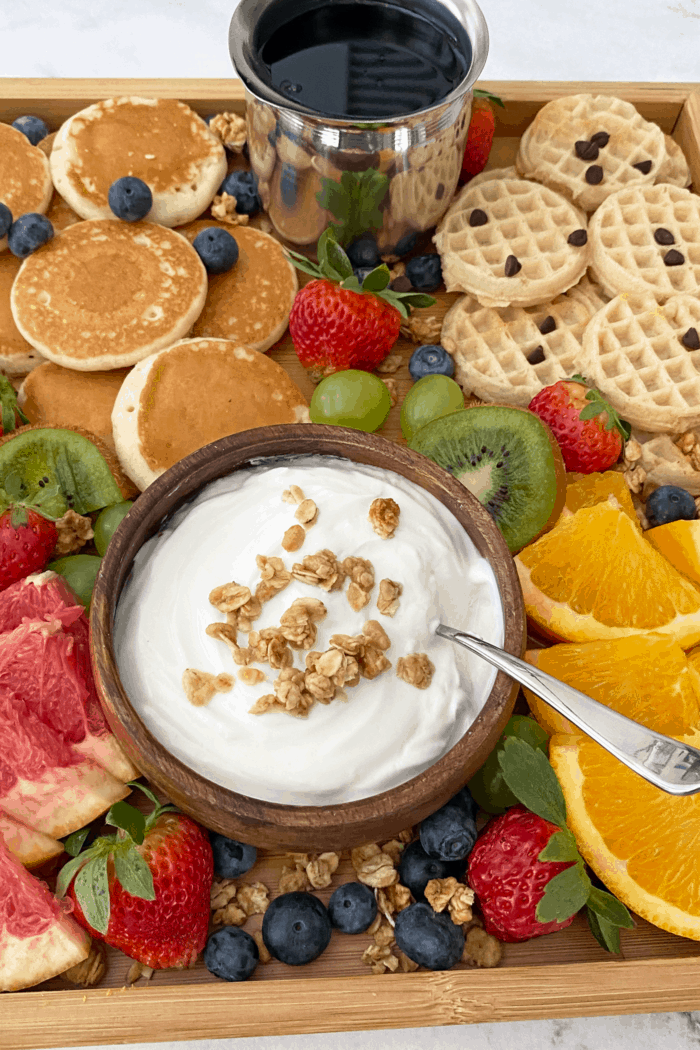 Close up of breakfast grazing board focusing on yogurt topped with granola.