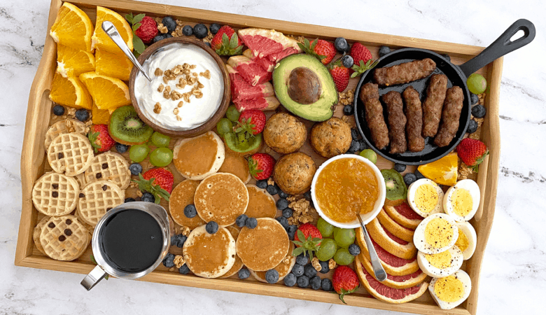 Overhead of breakfast grazing board filled with mini waffles, pancakes, fruit, hard-boiled eggs, sausage links, yogurt and more.