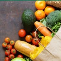 Paper grocery bag spilling over with fresh produce with text overlay