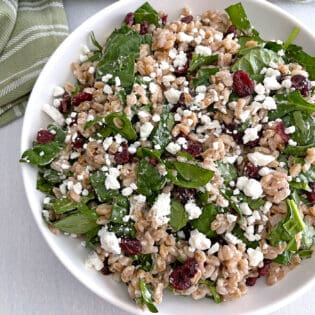 Overhead of farro salad in a white bowl with a green napkin.