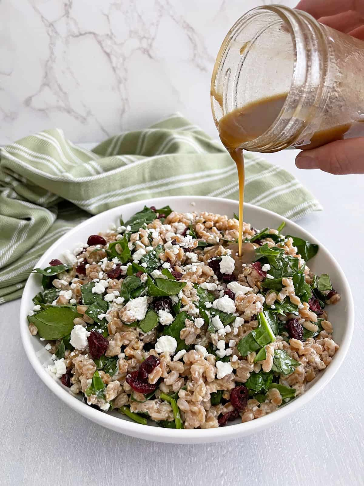 Dressing poured from mason jar over farro salad.