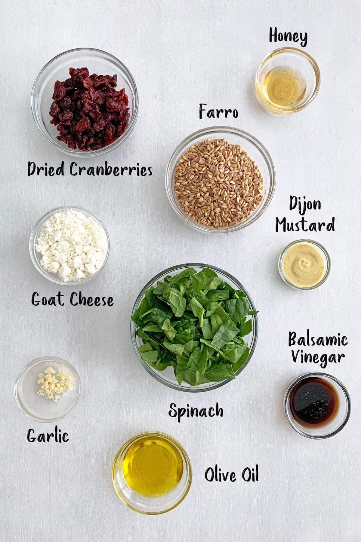 Ingredients for farro salad placed in individual bowls.