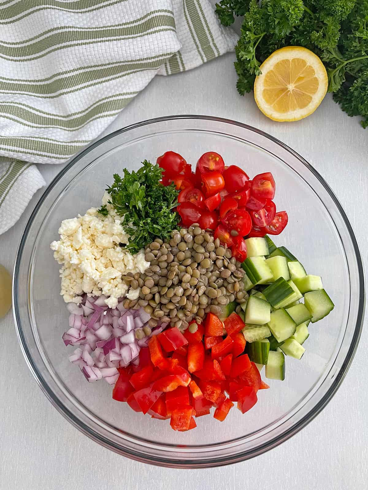 Lentils, bell peppers, cucumber, tomatoes, parsley, feta, and red onion in bowl.