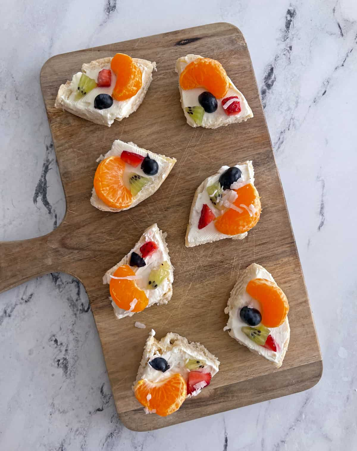 Fruit bagels with cream cheese on snackboard
